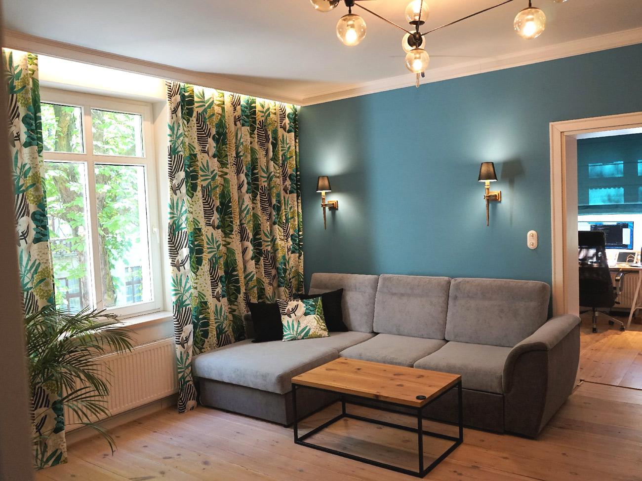 Pokój dzienny z turkusową ścianą i kolorowymi zasłonami AKMO