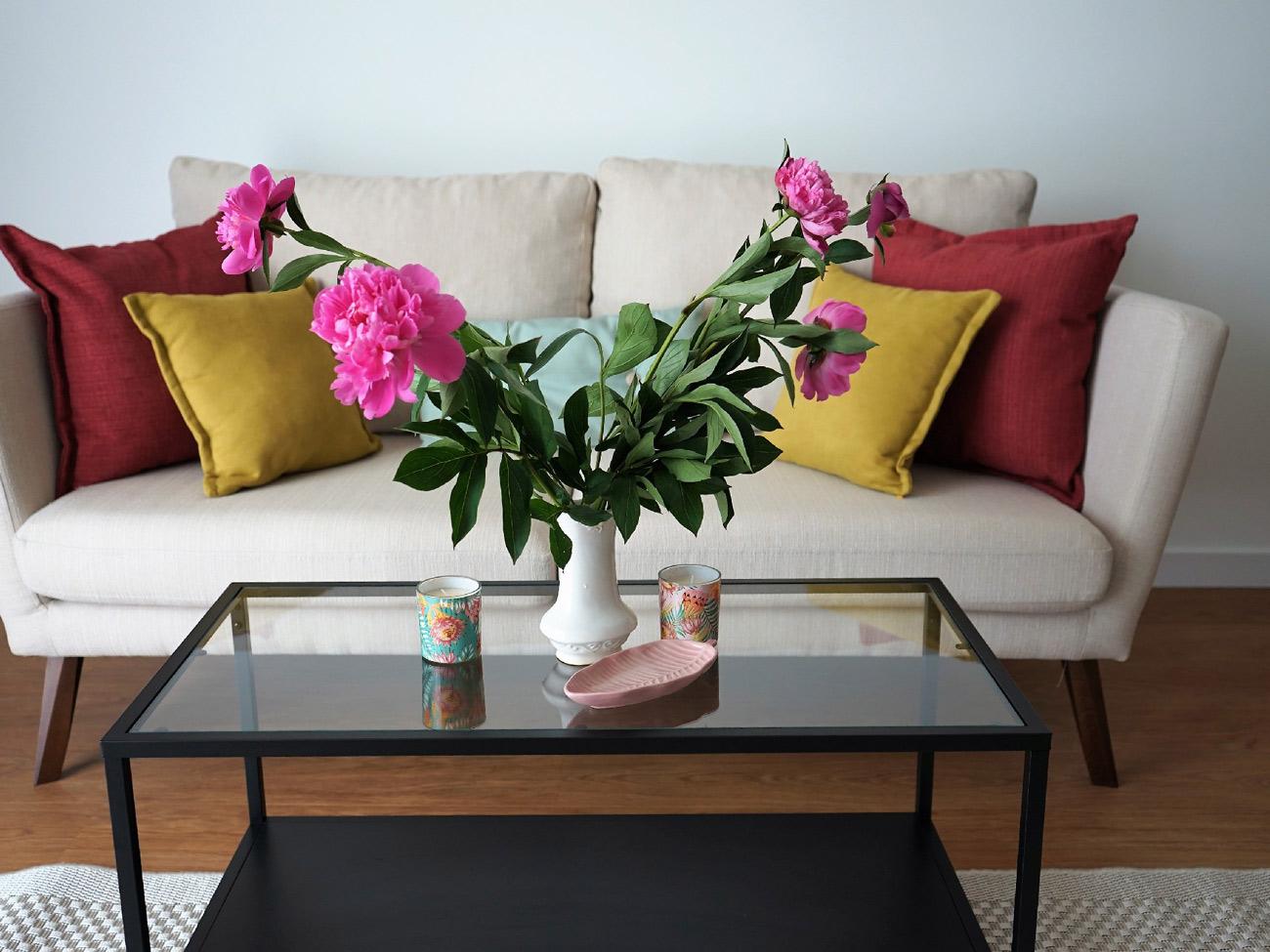 Jasna sofa z kolorowymi poduchami AKMO