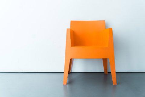 pomarańczowe krzesło na białej ścianie